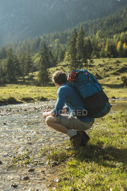 Austria, Tyrol, Tannheimer Tal, young hiker with backpack watching landscape — Stock Photo
