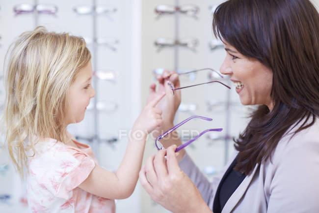 Fille monture lunettes avec mère à opticien boutique — Photo de stock