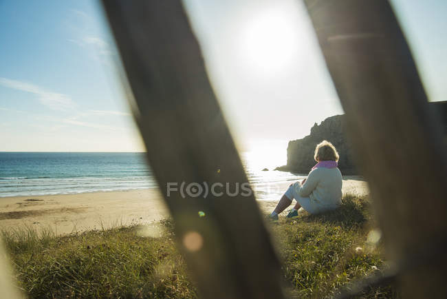 France, Brittany, Camaret-sur-Mer, senior woman sitting at the coast — Stock Photo
