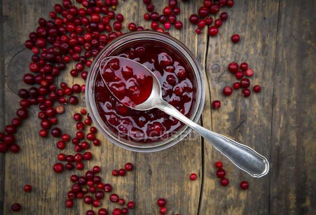 Lingonberries, Vaccinium vitis-idaea, num frasco de conservação e na colher, elevou a vista — Fotografia de Stock