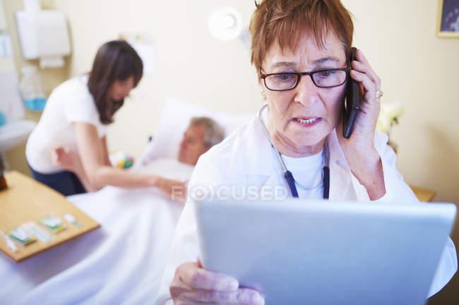 Врач с мобильным телефоном и цифровым планшетом в больничной палате — стоковое фото