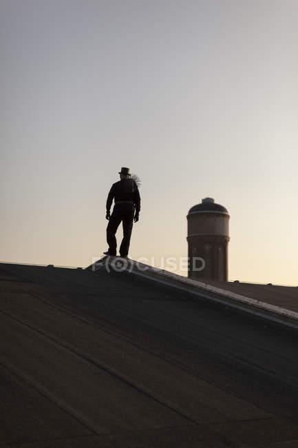 Silhouette di spazzacamino in piedi sul tetto al crepuscolo — Foto stock