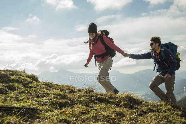 Austria, Tyrol, Tannheimer Tal, young couple hiking hand in hand on alpine meadow — Stock Photo