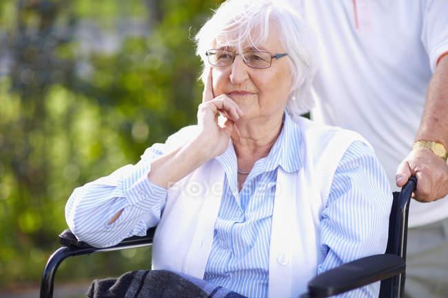 Homme poussant femme âgée en fauteuil roulant — Photo de stock
