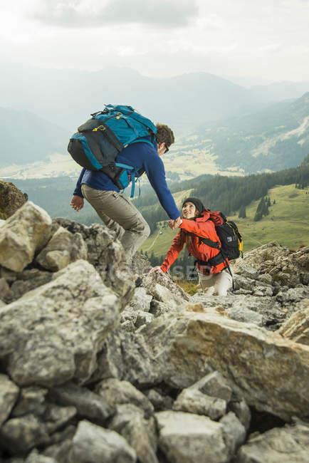 Austria, Tirolo, Tannheimer Tal, coppia di giovani escursionisti sulle rocce — Foto stock
