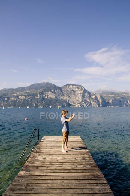 Italy, Veneto, Brenzone sul Garda, Boy taking pictures with smartphone — Stock Photo