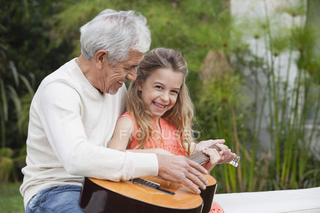 Grandfather and granddaughter with guitar outdoors — Stock Photo