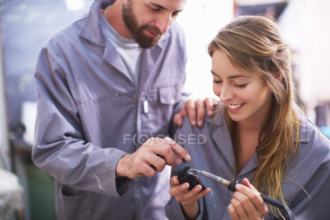 Craftspeople removing defects from rubber sculpture with soldering iron — Stock Photo