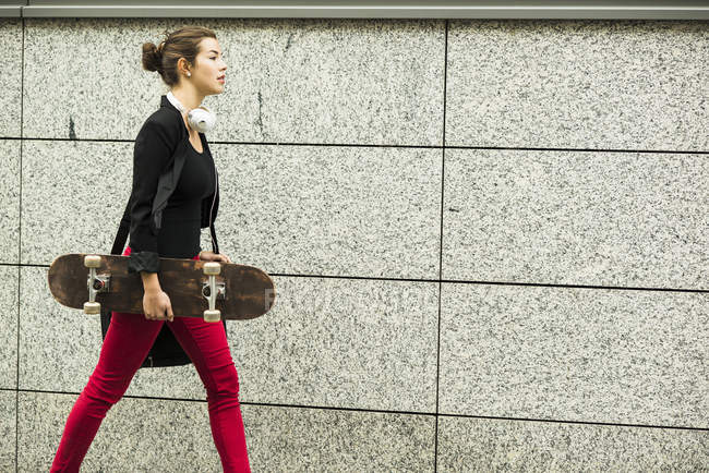 Woman with headphones and skateboard — Stock Photo