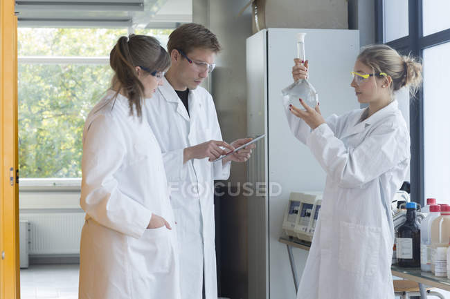 Three chemists working in a chemical laboratory — Stock Photo