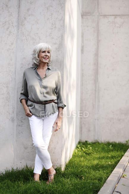 Улыбаясь белый волосы старшие женщины, прислонившись бетонную стену — стоковое фото