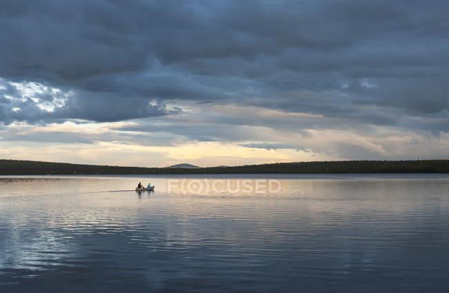 Suécia, Lapônia, Condado de Norrbotten, Kiruna, pai e filho canoagem sob céu tempestuoso — Fotografia de Stock