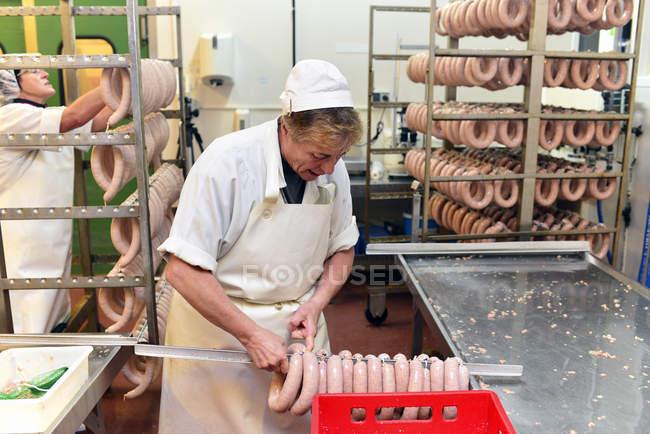 Старший жінка, поклавши ковбаси на шпажці для лікування на бійня — стокове фото