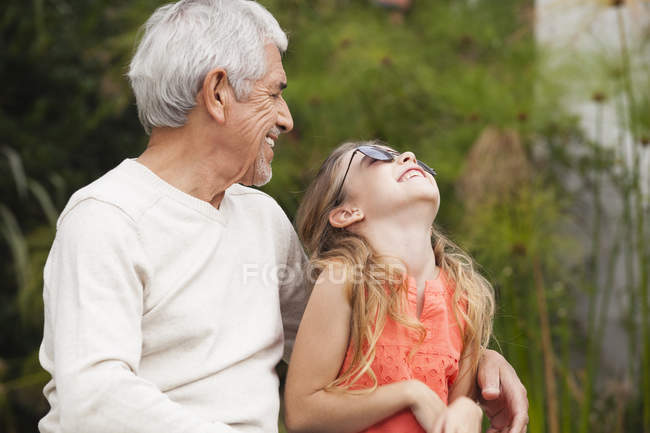 Grandfather and happy granddaughter with sunglasses outdoors — Stock Photo