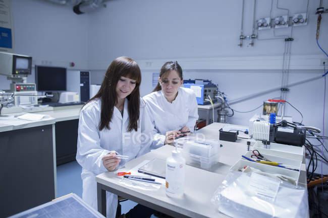 Dos técnicas femeninas trabajando juntas en un laboratorio técnico - foto de stock
