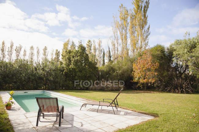 Стулья у бассейна в саду — стоковое фото