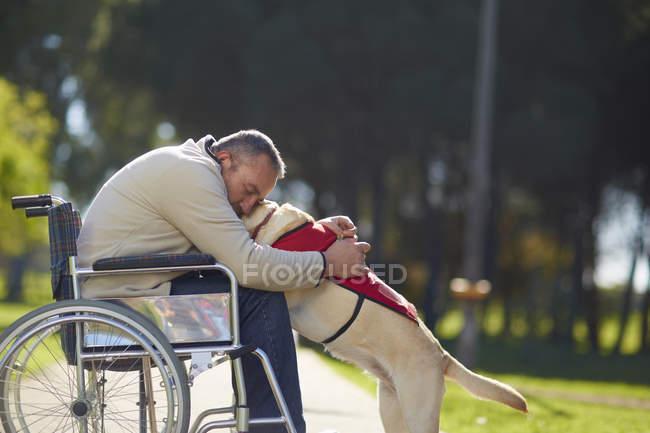Uomo in sedia a rotelle che abbraccia cane nel parco — Foto stock