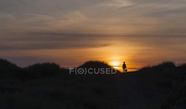 Силует дівчини в дюни на заході сонця — стокове фото