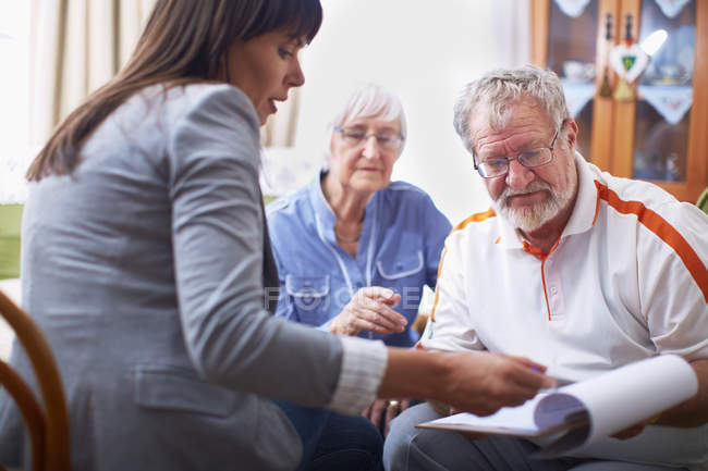 Mature Woman explaining document to senior couple — Stock Photo