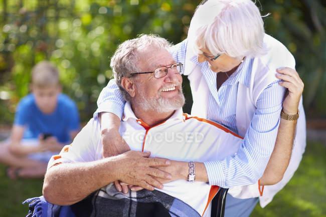 Старшие женщины охватывает мужа в инвалидной коляске — стоковое фото