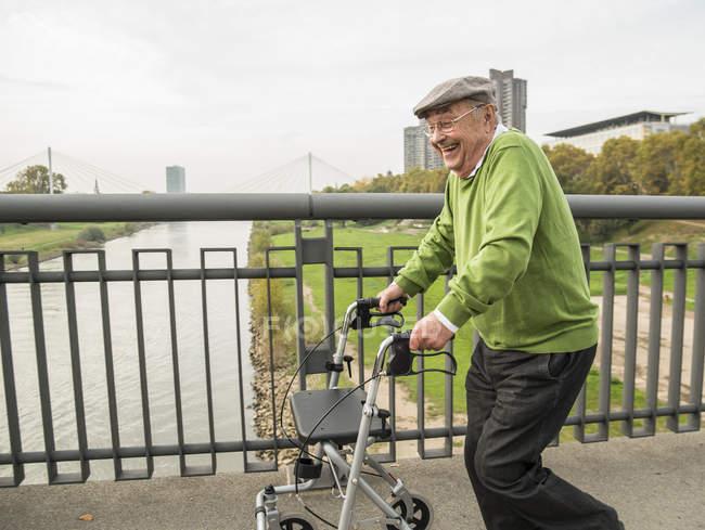Playful senior man with wheeled walker on bridge — Stock Photo