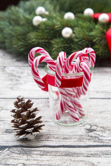 Grinalda de advento, cone de abeto e vidro de canas de açúcar em madeira — Fotografia de Stock