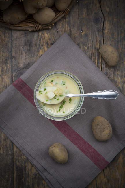 Вид зверху скла з картопляний суп гарнір з цибулею і грінками на дерев'яні таблиці — стокове фото