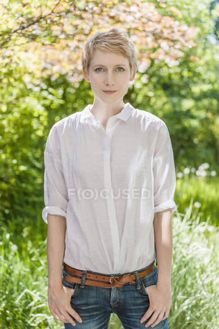 Portrait of woman with short blond hair with hands in pockets — Stock Photo