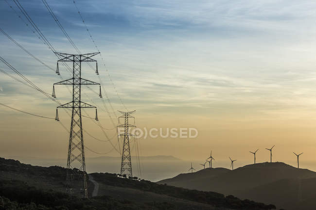 Spain, Andalusia, Tarifa, Wind farm and power pylons in the evening light — Stock Photo