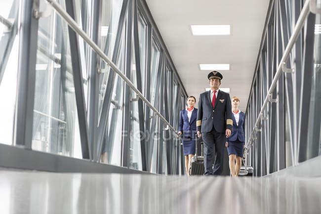 Piloto y dos asistentes de vuelo en el aeropuerto - foto de stock