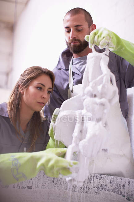 Craftspeople preparing ceramic shell around casting mold — Stock Photo