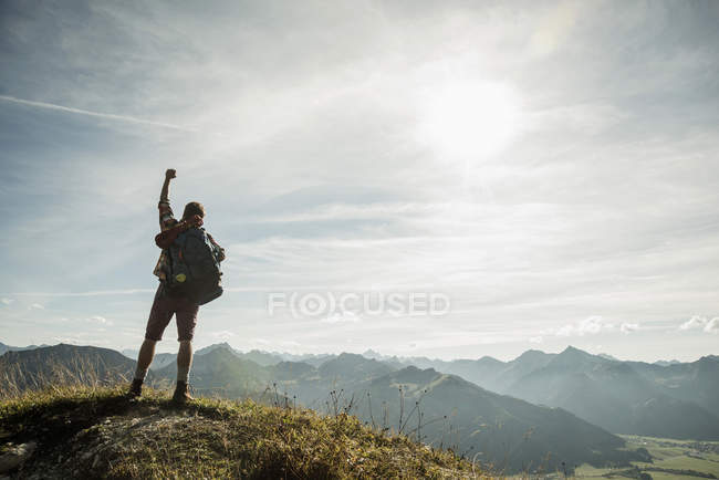 Austria, Tyrol, Tannheimer Tal, young man cheering on mountain top — Stock Photo