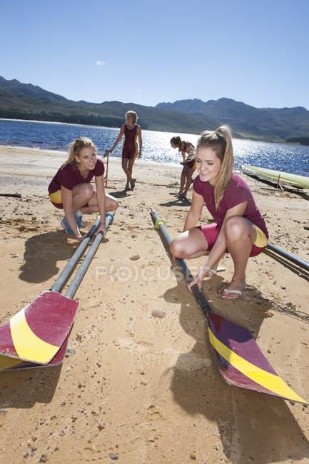 Четыре женщины гребцы кладут весла на берег озера — стоковое фото