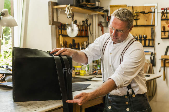 Saddler adjusting straps for leather rucksack — Stock Photo