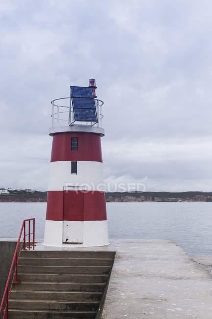 Vue sur le phare au bord de la côte — Photo de stock