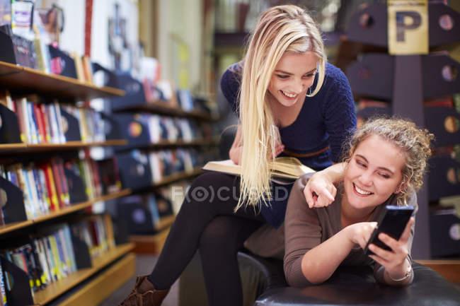 Zwei glückliche Studentinnen mit Handy in einer Bibliothek — Stockfoto
