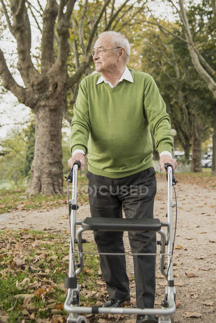 Senior man with wheeled walker in park — Stock Photo