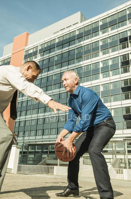 Два бизнесмена играют в баскетбол возле офисного здания — стоковое фото