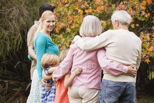 Extended family embracing in garden — Stock Photo
