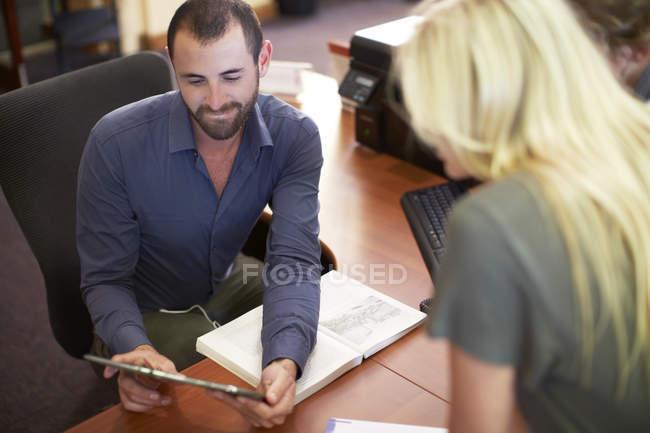 Bibliothécaire assistant et étudiant dans une bibliothèque regardant tablette numérique — Photo de stock