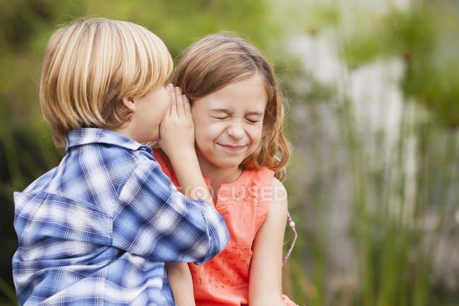 Chico susurrando en el oído de chica - foto de stock