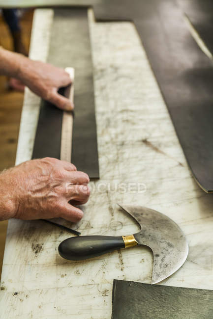 Saddler cutting piece of leather with head knife — Stock Photo