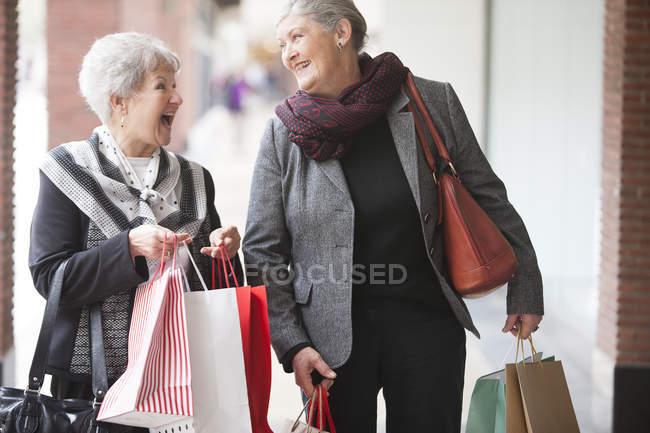 Two laughing senior women on shopping trip — Stock Photo