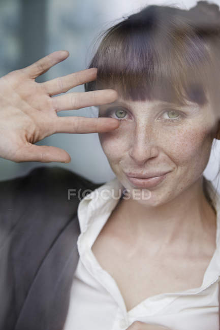 Portrait of smiling woman behind glass pane — Stock Photo