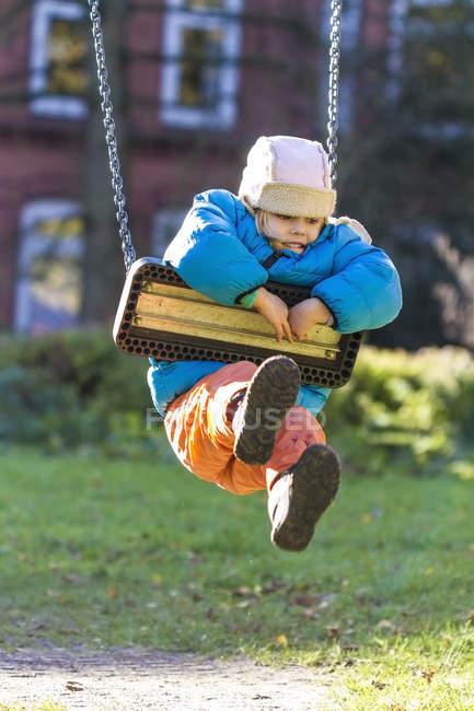 Girl hanging on swing — Stock Photo