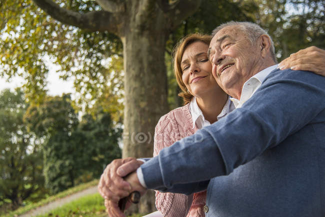Daughter embracing senior man outdoors — Stock Photo