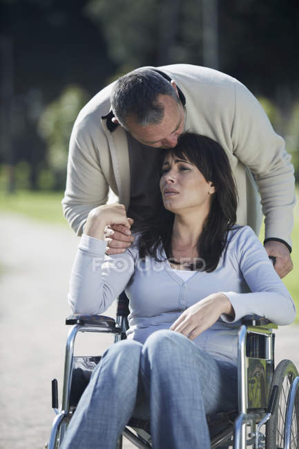 Man consoling sad woman in wheelchair — Stock Photo