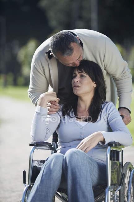 Мужчина утешает грустную женщину в инвалидном кресле — стоковое фото