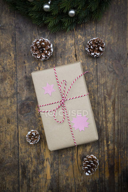 Wrapped Christmas present and fir cones on dark wood — Stock Photo