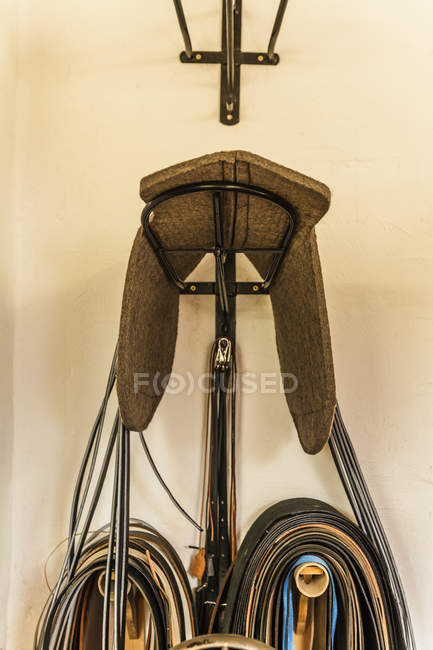 Saddle pad on stand and cut leather straps in saddlery — Stock Photo